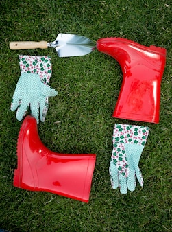 Closeup garden gloves, spade and red rubber boots lying on green grass