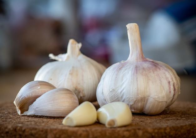 Primo piano del bulbo dell'aglio e dei chiodi di garofano su una tavola di sughero rotonda
