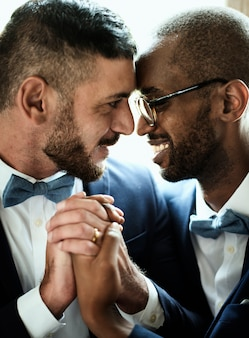 Closeup of gay couple smiling holding hands together