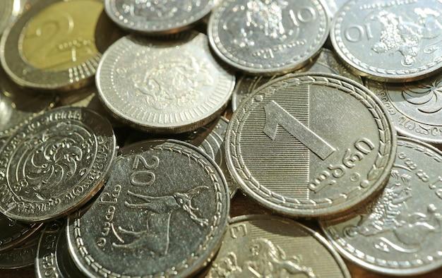 Closeup of georgian 1 lari and 20 tetri coins on another coin pile