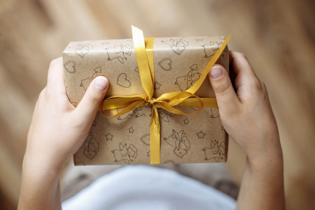 Closeup of a gift box in the hands of a child