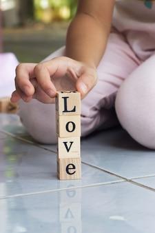 愛の言葉で木製ブロックを構築クローズアップ女の子手。
