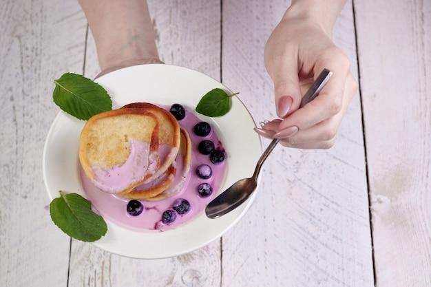 Рука девушки крупного плана держит белую тарелку с оладьями, налитыми йогуртом с кусочками черники и мяты. с другой стороны, чайная ложка - прекрасный завтрак и отличное начало дня.