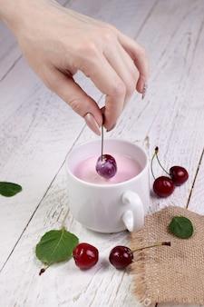 クローズアップの女の子の手は、ヨーグルト、軽い木製のテーブルとガラスの上に新鮮な桜を保持します。おいしい朝食と一日の素晴らしいスタート
