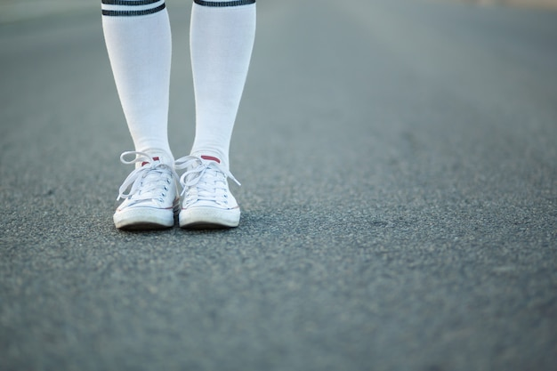 Closeup girl legs in white stockings stand alone on asphalt