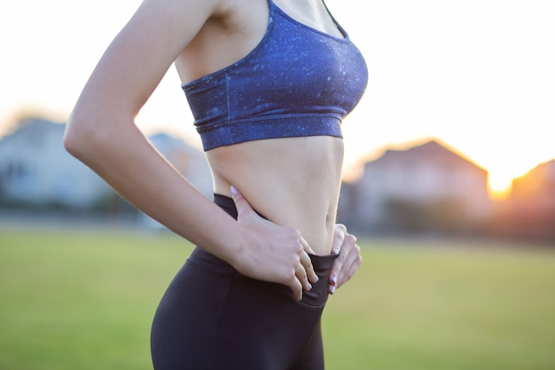 Closeup of a girl slim body in sports clothes. flat stomach as result of physical training.
