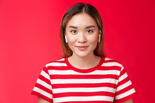 근접 촬영 매력 매력적인 현대 아시아 금발 소녀는 무선 흰색 이어폰을 착용하고 기쁘게 웃고 있습니다.