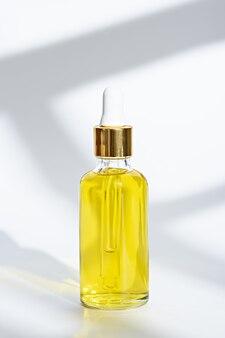 白い背景の上の化粧品の黄色いオイルとピペットとクローズアップガラス瓶