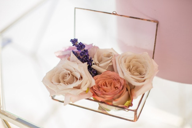 Closeup glass box for wedding rings decorated with fresh rose flowers and banch of lavender