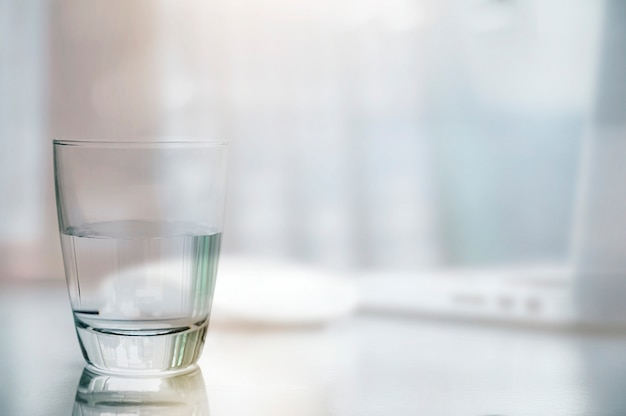 Closeup glass of clean water on white table with blurred image of laptop and mouse background.