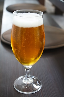 Closeup of a glass of light beer on the bar