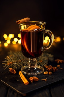 Closeup glass of mulled wine with orange and cinnamon on dark black background