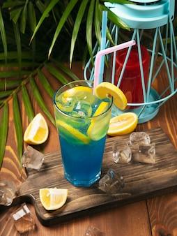 お祝いバーのカウンターで石灰で飾られた青いラグーンカクテルのクローズアップガラス。