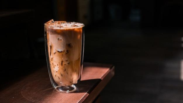 Крупным планом стакан кофе со льдом с молоком на столе