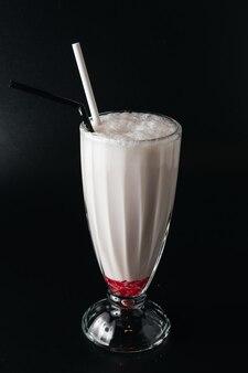 Крупным планом стакан молочного коктейля, изолированные на черной поверхности