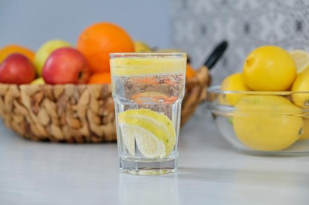レモンとスパークリングウォーターのクローズアップグラス。キッチンの背景に果物。