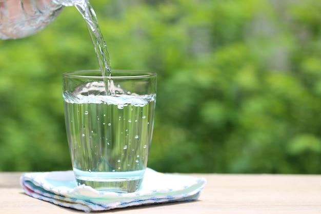 テーブルの自然空間に水のクローズアップグラス