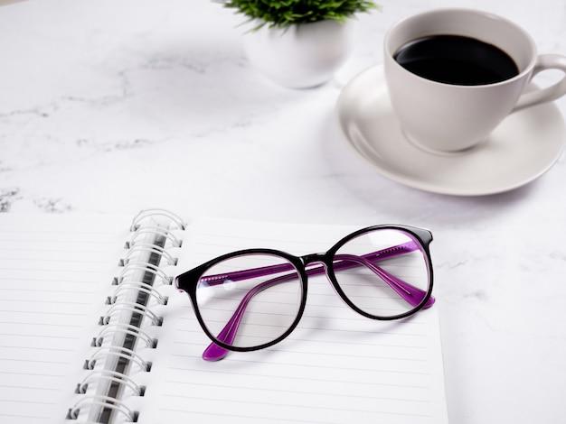 大理石の背景にコーヒーカップと空白のページノートブックのクローズアップメガネ