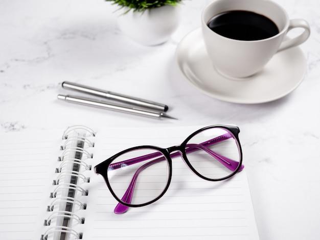 大理石の背景に銀のペンとコーヒーカップと空白のページノートブックのクローズアップメガネ