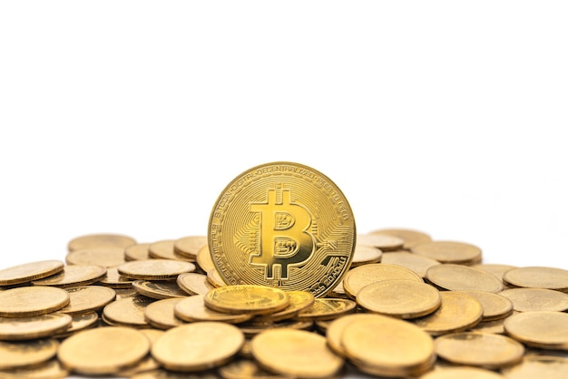 Closeup of gold bitcoin coin with pile of coins