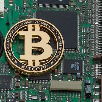 Closeup of gold bitcoin, computer circuit board and microchips