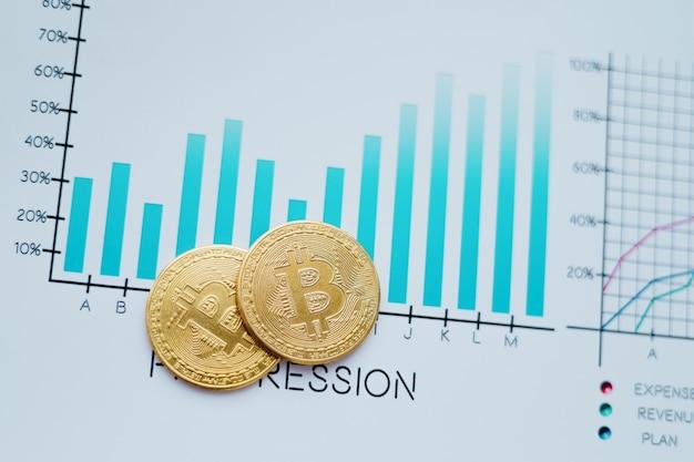Closeup gold bitcoins and a financial chart on the desktop