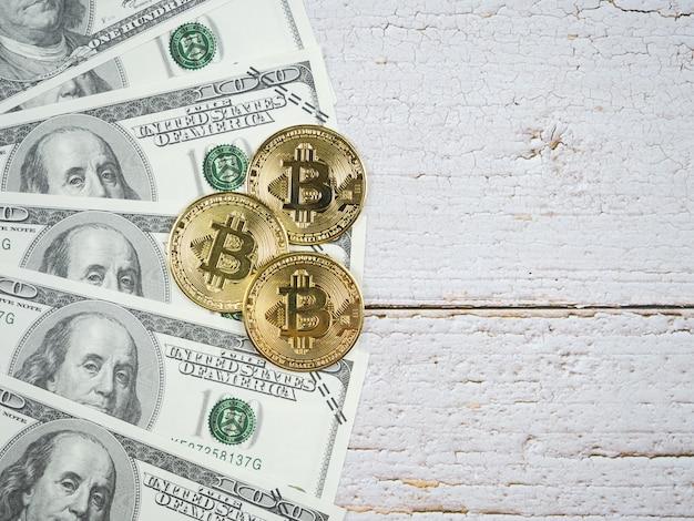 Золотые биткойны крупным планом на кучу денег на деревянном столе с копией пространства