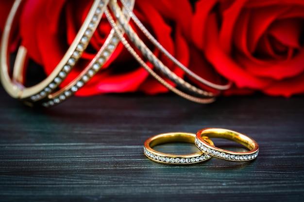 Жемчужина алмаза золотого кольца крупного плана. золотые обручальные кольца с бриллиантом и красной розой