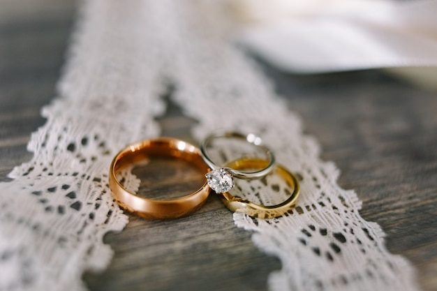 Closeup of gold wedding rings and white gold rings for the bride on white lace
