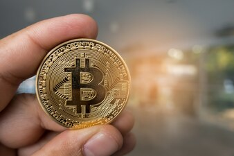 Closeup Golden bitcoin coin in a business office.
