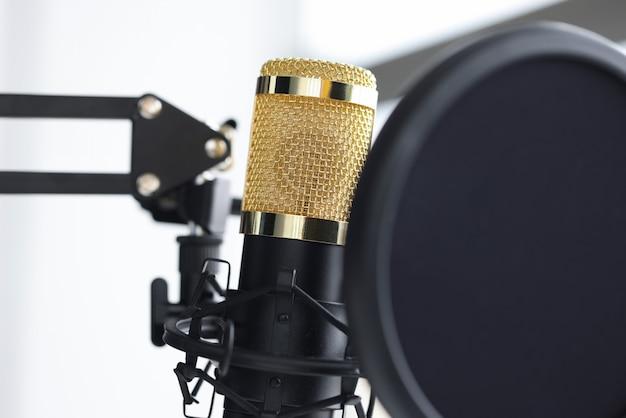 Closeup of golden microphone in recording studio