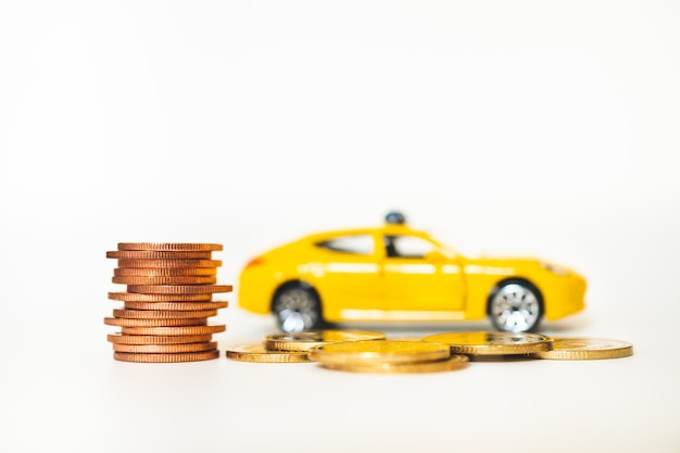 Closeup golden stack coins with yellow car background