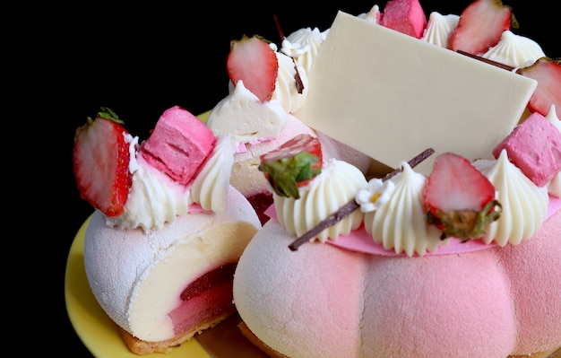Closeup a gorgeous fresh strawberry mousse cake with blank white chocolate greeting card