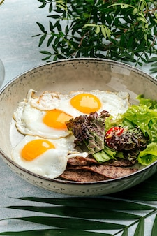 Closeup on gourmet fried eggs with roast beef and salad