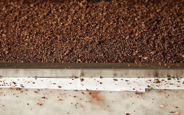 Primo piano granuloso noci su stampo riempito con massa di cioccolato fuso. preparazione di una gustosa torta di cioccolato biologico in vendita in pasticceria artigianale