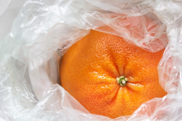 Closeup of a grapefruit wrapped in a white plastic bag.