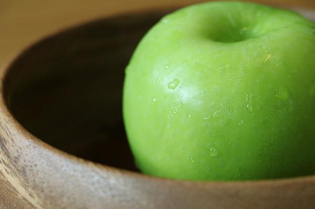 木製のボウルにクローズアップ青リンゴ