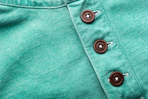 Closeup of green cloth with plastic buttons
