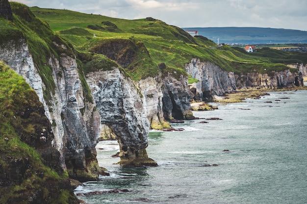 Крупным планом зеленый покрытый утес береговой линии северной ирландии потрясающий обзор спокойствия ирландского залива