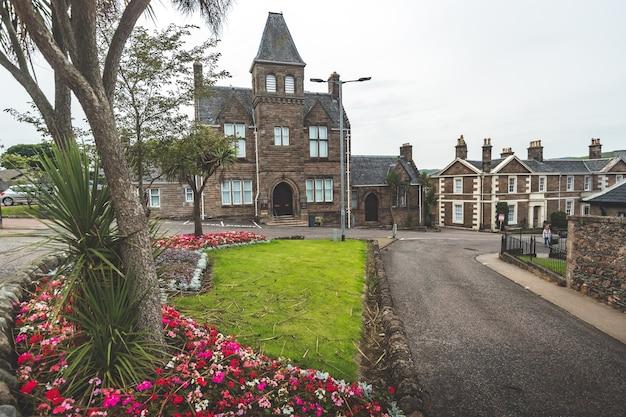 빈티지 건물 앞의 근접 촬영 녹색 꽃 잔디 복고에서 북 아일랜드 매력적인 풍경