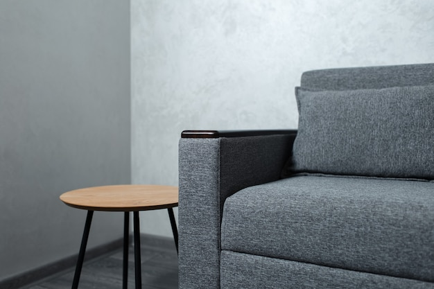 Closeup of grey sofa and small wooden table in apartment.
