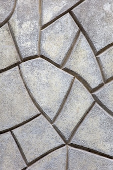 Closeup of grey stone wall made of of irregular geometric shapes background