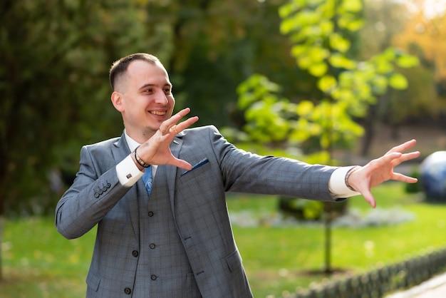 青いネクタイと灰色のスーツのクローズアップ新郎男は目をそらし、花嫁を待つ