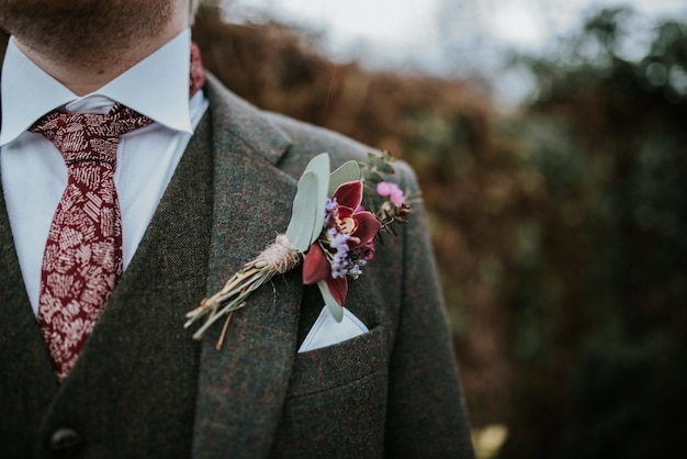 Closeup of a groom's suit with flowers and red patterned tie with trees on the background