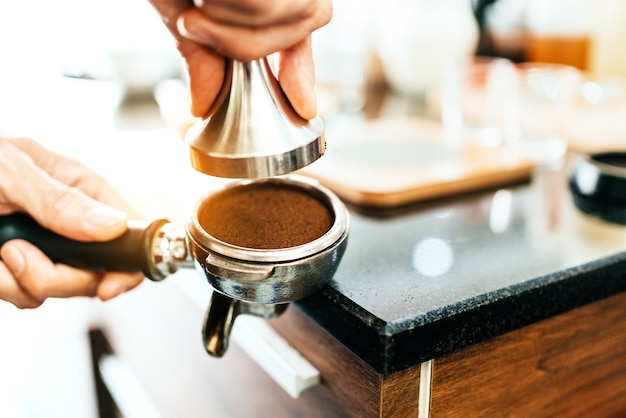 Closeup ground coffee bean in metal filter with handle holding by woman hand