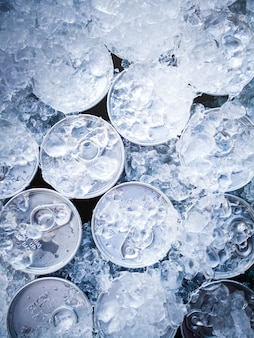Closeup of a group of drink can iced submerged in frost ice background