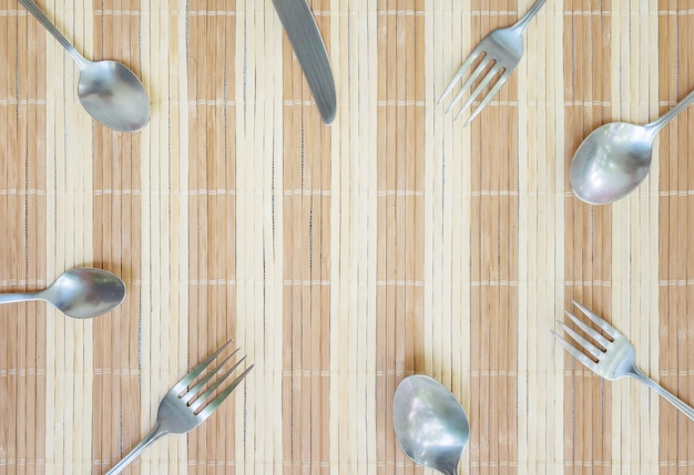 Closeup group of  stainless fork spoon and knife on wood mat textured