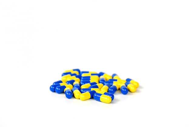 Closeup group of yellow and blue capsule medicine on white.