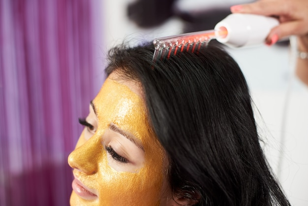 Closeup of hair treatment procedure performed to a brunette client of a beauty salon who has a gold mask on her face.