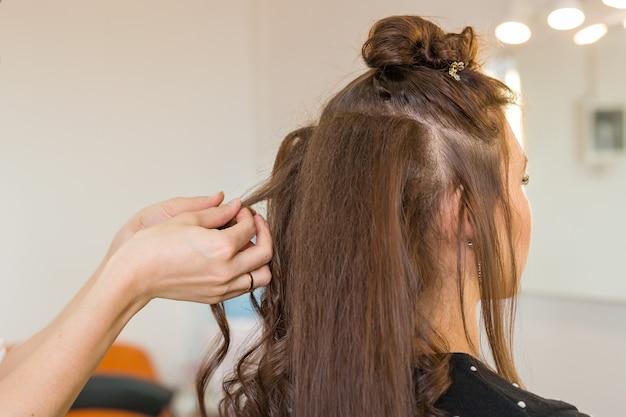 근접 촬영 미용사 coiffeur는 젊은 여성을 위한 헤어스타일을 만든다